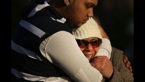 Zulma Sein is hugged by a family member outside of the entrance to the Sandy Hook School on Saturday.