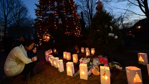 Candles burn next to a lighted tree at a makeshift shrine in Newtown, Connecticut, commemorating the victims of the mass shooting at Sandy Hook Elementary School on December 14, 2012.