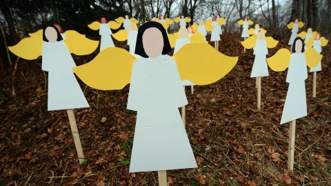 Angel wood cutouts for each of the 27 victims are set up on hillside in Newtown on December 16.