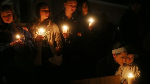 Left to right: Newtown residents Claire Swanson, Kate Suba, Jaden Albrecht, Simran Chand and New London, Connecticut residents Rachel Pullen and her son Landon DeCecco, hold candles at a memorial for victims on the first Sunday following the mass shooting at Sandy Hook Elementary School on December 16 in Newtown, Connecticut.