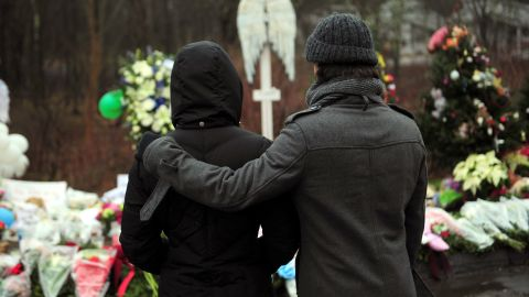 People pay their respects on Monday, December 17, at a memorial to the victims of an elementary school shooting in Newtown, Connecticut.