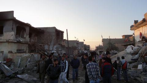 Iraqis inspect the damage following two bomb blasts in Tuz Khurmatu in the Kirkuk province on December 17, 2012.