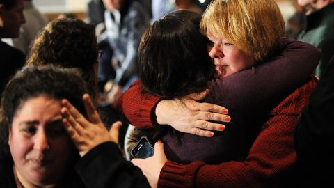 Mourners comfort one another December 16 before U.S. President Barack Obama speaks at an interfaith vigil for the shooting victims.