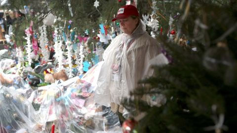 A woman pauses at a streetside memorial during a moment of silence on December 21 in Newtown.