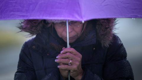 A woman bows her head in Newtown's Sandy Hook village on December 21.