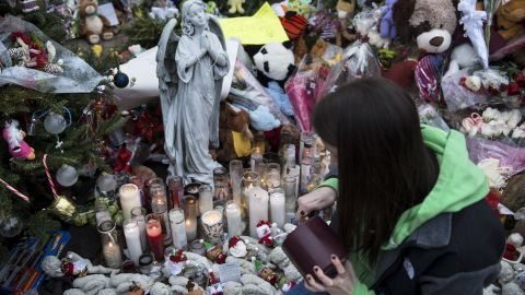 A woman lights a candle at a makeshift memorial on December 20, 2012 in Newtown, Connecticut. People continue to mourn the killing of 20 students and 6 adults by gunman Adam Lanza at Sandy Hook Elementary School last Friday.  AFP PHOTO/Brendan SMIALOWSKI        (Photo credit should read BRENDAN SMIALOWSKI/AFP/Getty Images)
