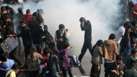 Demonstrators react as police fire tear gas on December 22.
