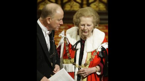 An usher helps Thatcher, now a baroness, to her seat during the state opening of Parliament in November 2009.