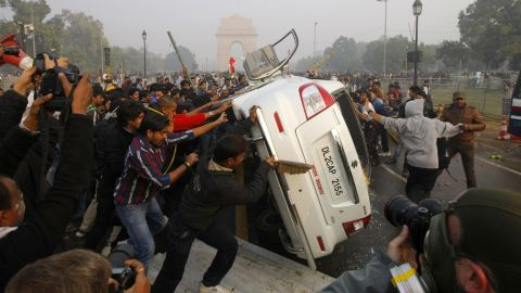 Demonstrators turn a car over on December 23.