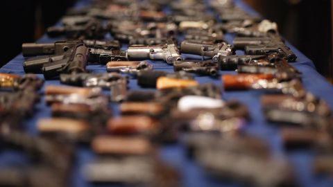 A table of illegal firearms confiscated in a large weapons bust in New York's East Harlem is on display at an October 12 news conference.