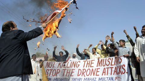 A Pakistani protester holds a burning U.S. flag as they shout slogans during a protest in Multan in 2012 against the US drone attacks in the Pakistani tribal region.