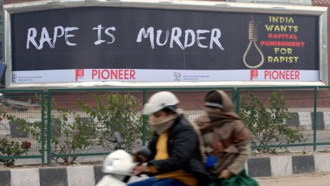 Female commuters ride a scooter past a billboard, calling for capital punishment against rape, in New Delhi on December 27, 2012.