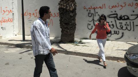 """Tunis residents walk past graffiti left by rioters on a building housing a controversial art exhibition in the Tunisian capital in June 2012. The graffiti  messages read: """"God is great,,"""" """"Non-believers have no place in Tunisia"""" and """"You are enemies of God."""""""