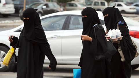 """In a picture taken November 19, 2012, Saudi women walk with their shopping bags and drinks outside the Olaya mall in Riyadh. Women in Saudi Arabia, who are veiled in public and banned from driving, face further restrictions with a new law allowing airport security to report their movements to their male """"guardians"""",  a move that is deemed by rights activists a form of """"slavery"""" as any Saudi woman intending to travel must carry a """"yellow slip"""" as a proof of consent granted to her."""