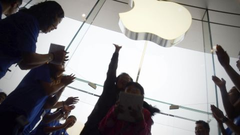 Apple staff welcome customers in the new Apple store at WangFujin business district in Beijing on October 20,2012. Apple opened its biggest Asian store yet in Beijing on October 20, with hordes of shoppers descending on the three-floor complex that highlights the growing importance of China to the US tech giant.