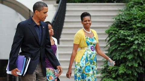 """Obama has been known to wear dresses from mass retailer Talbots and accessorize them with signature pieces such as this sweater from Dear Cashmere and a belt by Sonia Rykiel, worn in July 2009, <a href=""""http://mrs-o.com/newdata/2009/7/5/bon-voyage.html"""" target=""""_blank"""" target=""""_blank"""">according to Mrs. O</a>."""