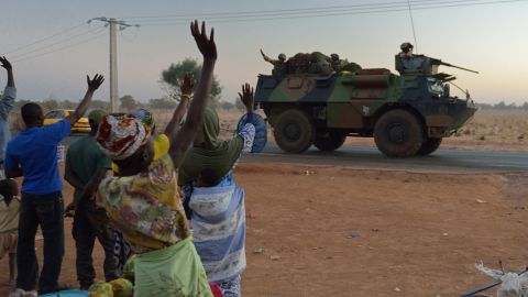 Malian people wave to French soldiers as a convoy of armoured vehicles leave Bamako and start a deployment to the north of Mali as part of the 'Serval' operations on January 15, 2013.