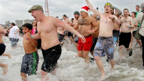 People run into the chilly water as they take part in the Coney Island Polar Bear Club's New Year's Day swim on January 1, 2013 in the Coney Island neighborhood of the Brooklyn borough of New York City. The annual event attracts hundreds who brave the icy Atlantic waters and temperatures in the upper 30's as a way to celebrate the first day of the new year.