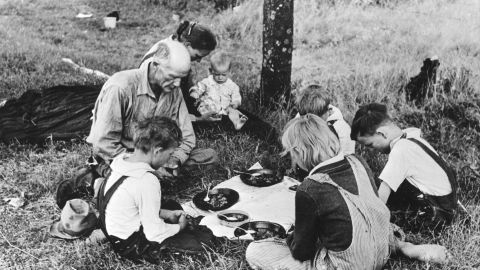 A migrant family prays before their noonday meal Oklahoma during the Great Depression.