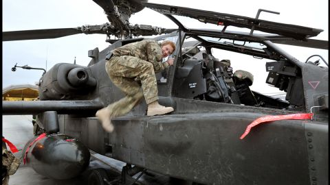 Harry climbs on board an Apache helicopter as part of a preflight check on December 12, 2012.