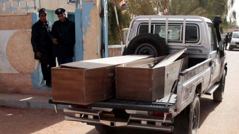 Algerian security personnel monitor as empty coffins are transported to collect victims that were killed during the hostage crisis at a desert gas plant in Algeria's deep south on January 21, 2012 in In Amenas.