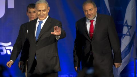 Israeli Prime Minister Benjamin Netanyahu (L) and ultra-nationalist Avigdor Lieberman (R) of the Likud-Beitenu coalition party greet supporters as they arrive on stage on elections night on January 22, 2013 at the party's headquarters in Tel Aviv. Netanyahu said it was necessary to form the 'broadest possible government' after his Likud-Beitenu list won a narrow election victory, with the centrist Yesh Atid in second place. AFP PHOTO / JACK GUEZ (Photo credit should read JACK GUEZ/AFP/Getty Images)