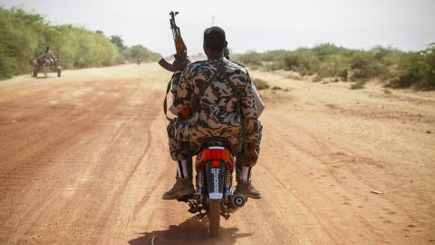 A soldier rides on the back of a scooter outside Diabaly on January 23.