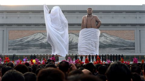A crowd watches as statues of North Korean founder Kim Il Sung and his son Kim Jong Il are unveiled during a ceremony in Pyongyang in April 2012.