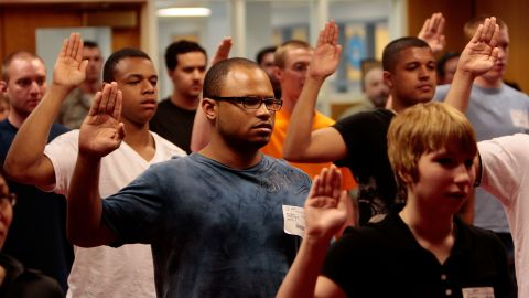 New U.S. military recruits take the Oath of Enlistment while their families and friends look on at Fort Hamilton in Brooklyn.