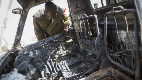 A Malian soldier looks at the wreckage of an Islamist rebel's armed pickup truck in Konna.