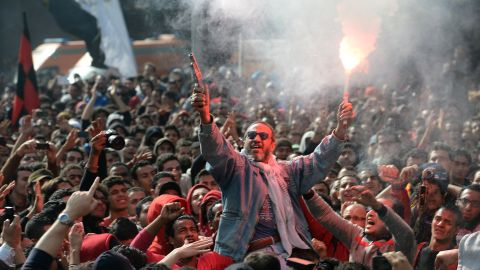 An Egyptian fan of Al-Ahly football club fires celebratory shots in the air and lights a flare as club supporters celebrate outside its headquarters in Cairo on January 26.