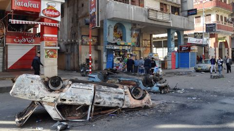 Egyptians walk past destroyed cars in Port Said on January 28 following the funeral of those killed in clashes.