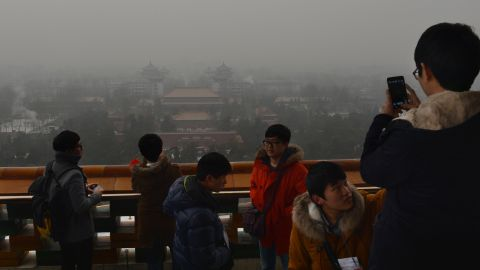 Japanese tourists take photos from the historic Jingshan Park as smog continues to shroud Beijing on January 31, 2013.  Doctors in Beijing said on January 31 that hospital admissions for respiratory complaints rose in recent days during the latest bout of air pollution to cover northern China.          AFP PHOTO/Mark RALSTON        (Photo credit should read MARK RALSTON/AFP/Getty Images)