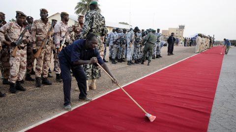 A man sweeps the red carpet at Mali's Mopti airport on January 2 before the arrival of Hollande and Mali's interim President Dioncounda Traore.
