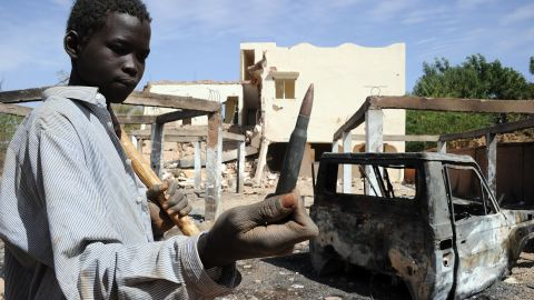A child holds up a machine gun round found in the ruins of a building destroyed by French airstrikes in Douentza, Mali, on February 5.