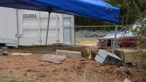 A tent covers the bunker where where a 5-year-old child was rescued by law enforcement after being held for nearly a week. FBI agents placed the blue tent over the bunker to protect evidence below.
