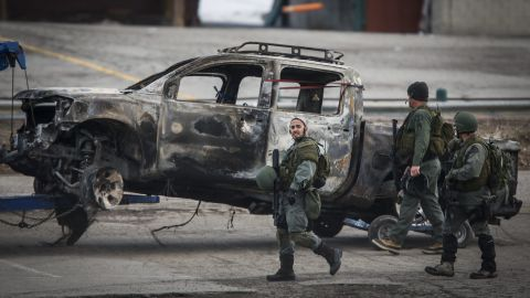 Officers investigate the burned out truck of Christopher Jordan Dorner that was discovered at the base of Bear Mountain Ski Resort in Big Bear Lake, California, on Thursday, February 7.