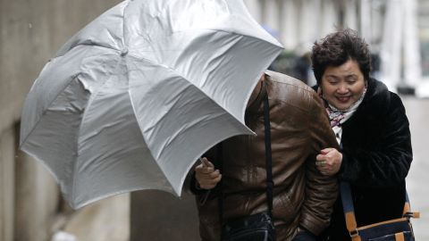 Tourists brave the high winds in New York's Financial District on February 8.