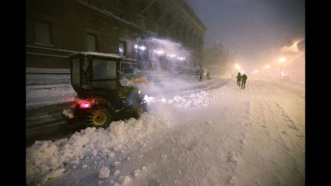 Snow is cleared in front of Boston Public Library on Friday.