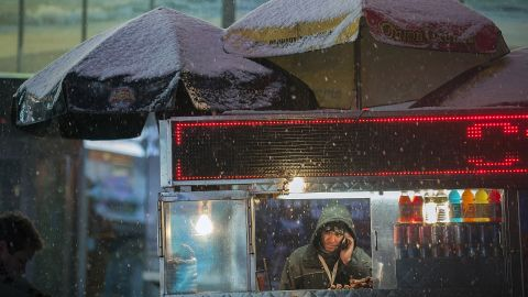A food vendor stands under his cart as snow falls in Times Square.