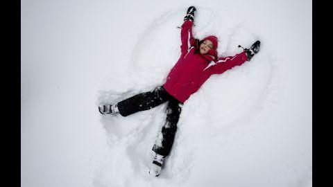 Phoebe Lightburn, 9, makes a snow angel in Central Park in New York.