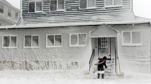 A man shovels snow along Winthrop Shore Drive in Winthrop, Massachusetts.