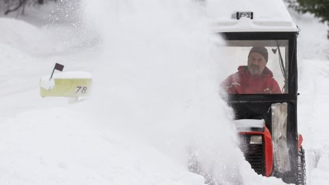 Paul DeCarlo uses a snow blower to clear the walk in front of his house in Greenfield, Massachusetts.