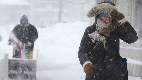 A woman walks through the snow as a worker clears snow from a sidewalk in the Back Bay neighborhood of Boston.