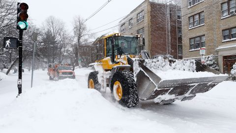 A front loader and truck drive down Warren Street in the Brighton neighborhood on Saturday in Boston.