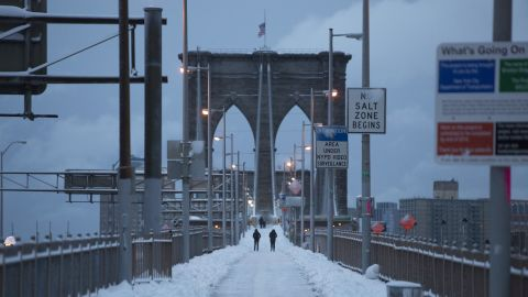 People walk along the Brooklyn Bridge following a major winter storm on Saturday in New York City. Possible record-setting blizzard conditions are expected with heavy snow warnings in effect from New Jersey through southern Maine.