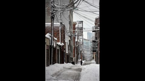A person walks through the snow in an alley in Hoboken, New Jersey, on Saturday.