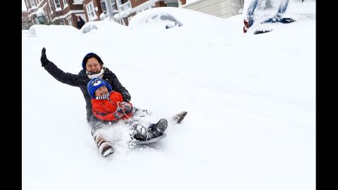 Josephine Sipayung and her son Eric, 6, sled down an empty street past snow-covered vehicles in Boston on Saturday.