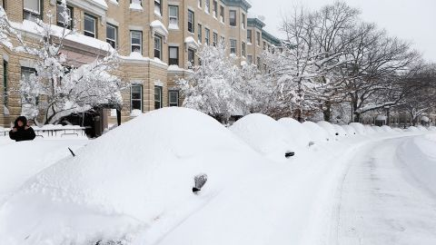 Snow-covered vehicles sit on Commonwealth Avenue in the Brighton neighborhood of Boston on Saturday.