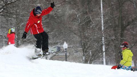 A boy snowboards in Boston Common on Saturday.